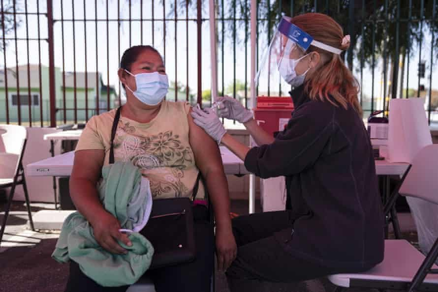Juanita Ortega, left, receives a Covid-19 vaccine from registered nurse Anne-Marie Zamora at a pop-up vaccine clinic in Los Angeles. Photograph: Jae C Hong/AP