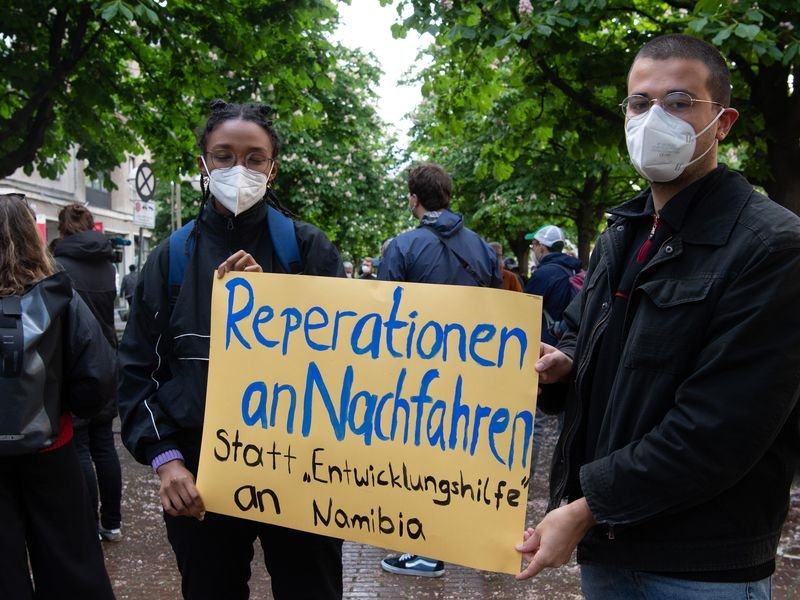 """Two protesters hold a sign reading """"Reparations to descendants instead of"""