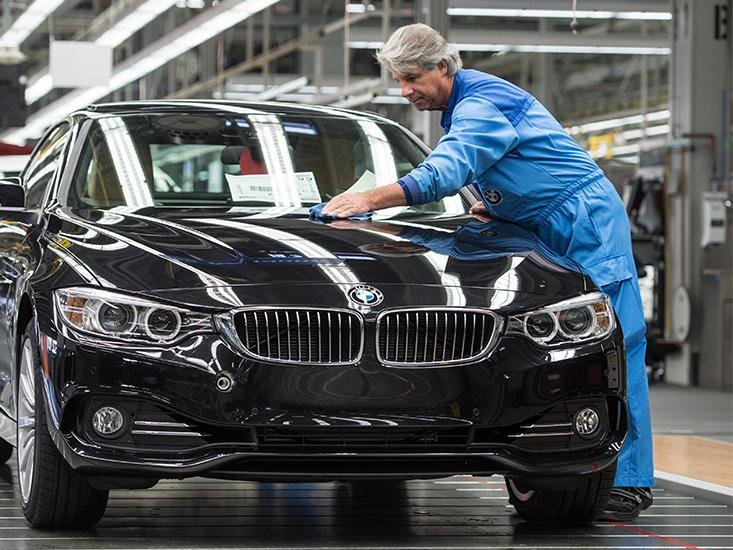 ADAPTING TO OLD: A worker polishes a BMW car at a plant in southern Germany. The company has found that simple ergonomic modifications to its assembly lines, such as chairs and custom shoes, increases the productivity of older workers.