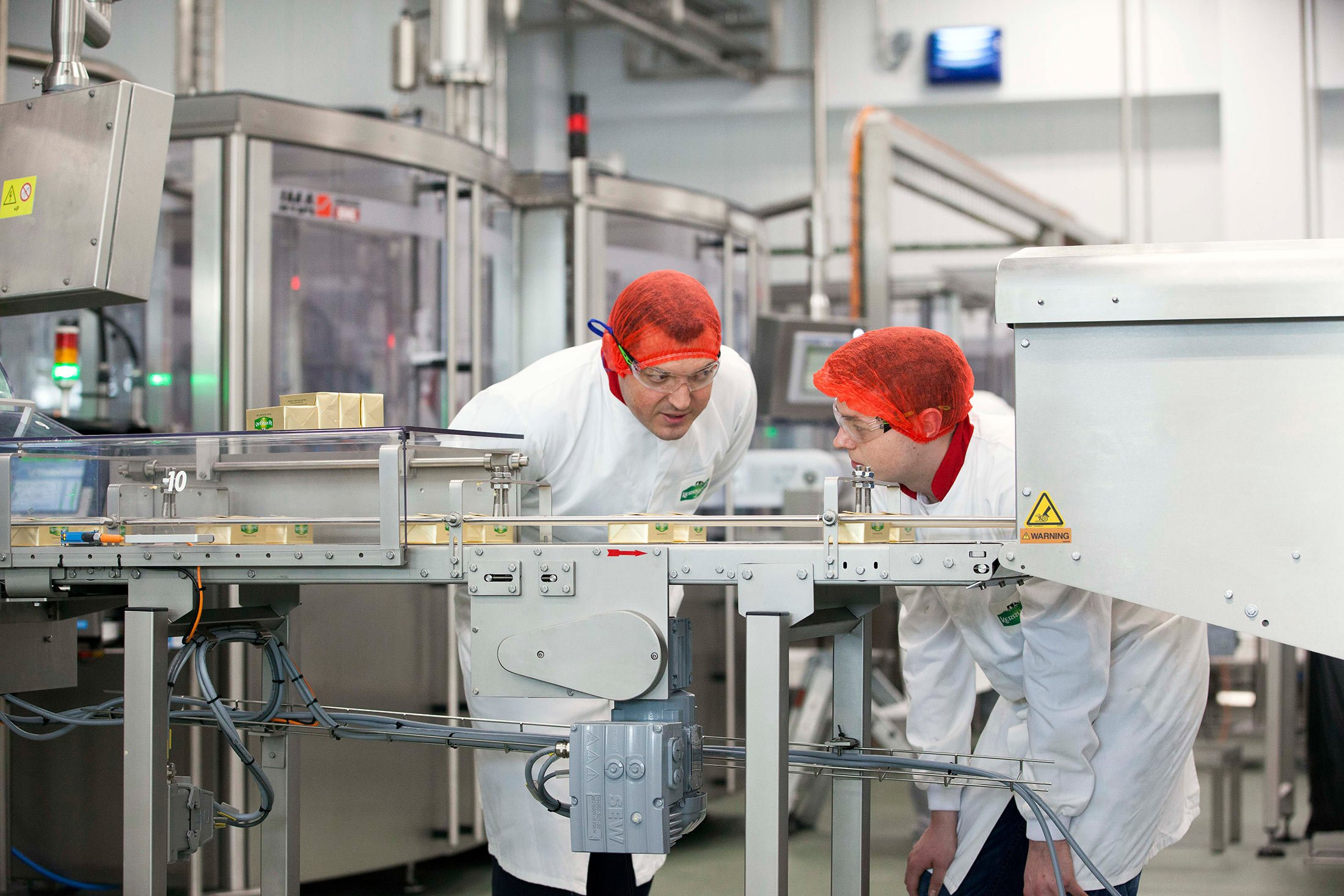 Employees inspect butter packages at Kerrygold Park.