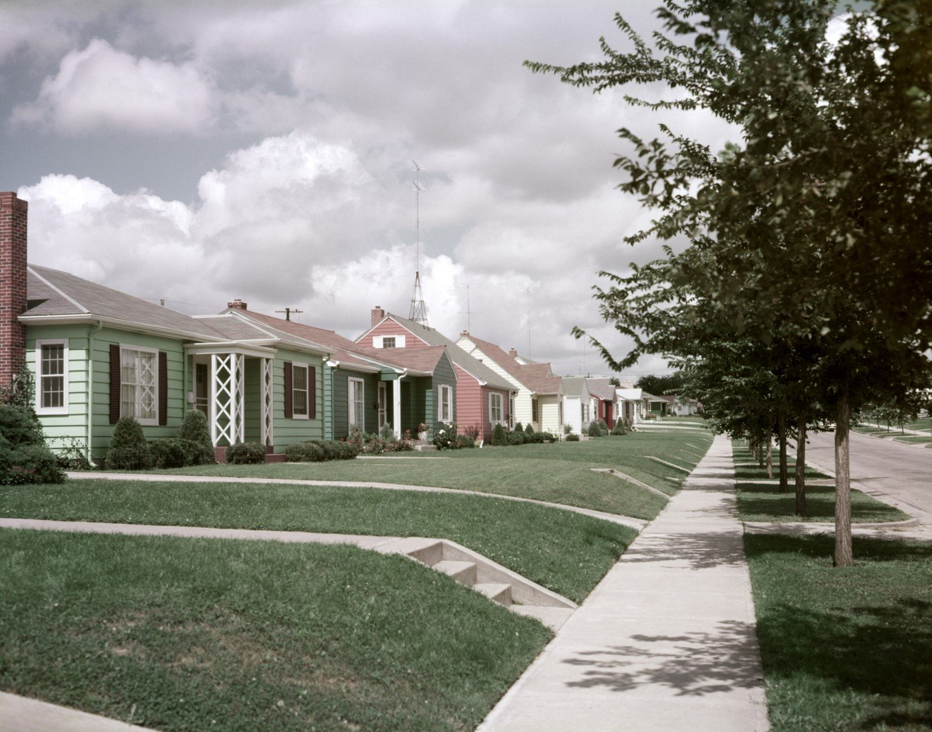 The houses may all look the same, but suburban communities, such as this Sioux Falls, South Dakota, block in 1952, also connected families along flowing streetscapes.