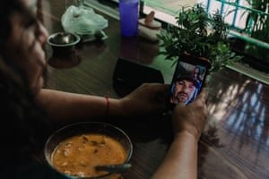 Esperanza Pacheco sharing a meal by video call with her husband. Photograph: Mariceu Erthal Garcia/The Marshall Project