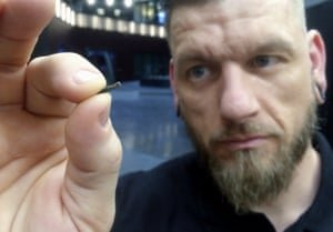 Österlund holds a small microchip implant. Photograph: James Brooks/AP