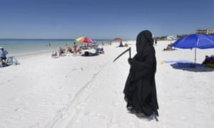 Daniel Uhlfelder, a Florida attorney dressed as the Grim Reaper, walks along the newly opened beach near Destin, Florida, on 1 May. Photograph: Devon Ravine/AP