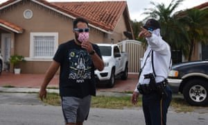 A policeman directs a citizen where to pick up an unemployment form in Miami, Florida, earlier this month. Photograph: Michele Eve Sandberg/Rex/Shutterstock