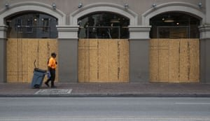 A worker walks past a boarded up store in New Orleans on 8 April. Photograph: Sophia Germer/Bloomberg via Getty Images