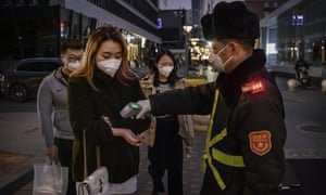 'Shouldn't we wait to see the China situation? They have contained the epidemic after seven weeks of intensive national effort.' A woman in Beijing has her temperature checked before entering a shopping mall. Photograph: Kevin Frayer/Getty Images