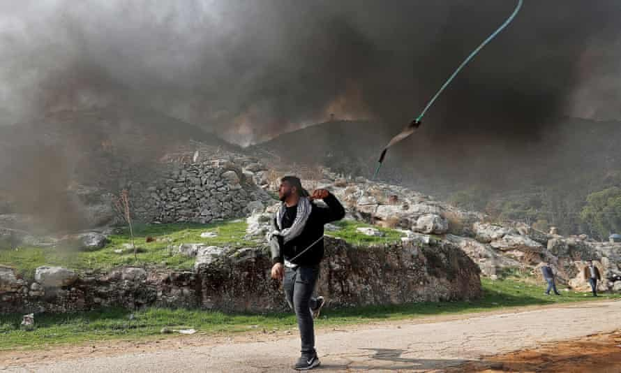 A Palestinian demonstrator hurls stones at Israeli troops during a protest against Jewish settlements. Photograph: Mohamad Torokman/Reuters
