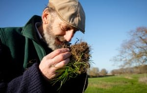 John Cherry of Weston Park Farms inspects and smells the soil in one of his fields. Photograph: David Levene/The Guardian