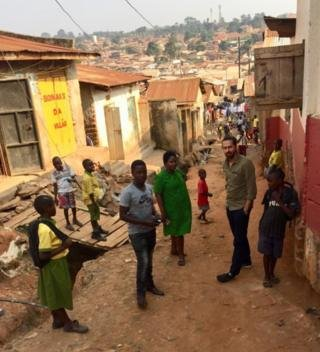 Image caption                                      Daniel, Prudence and Jamie with children in the poor area of Kampala where Prudence works as a nurse