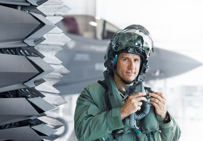 Lieutenant Colonel David Berke stands next to the engine of the F-35B.