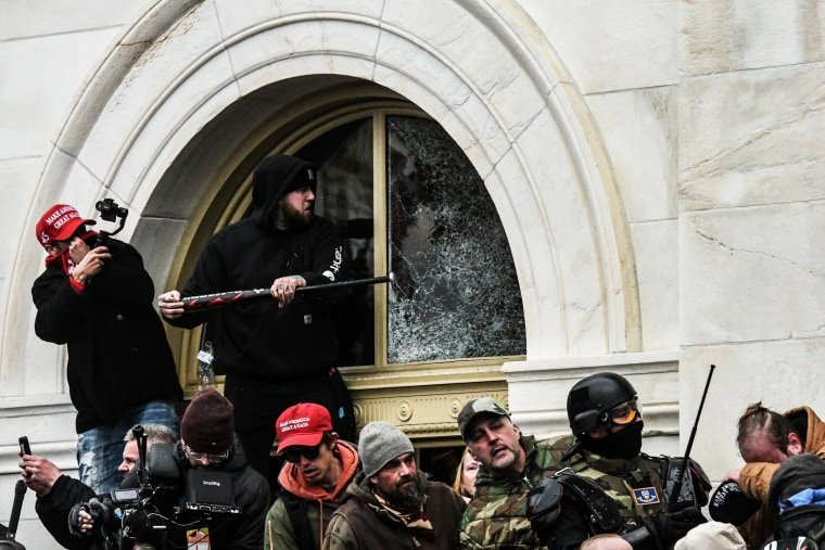 A rioter smashes a window with a baseball bat at the U.S. Capitol on Wednesday.Stephanie Keith / Reuters