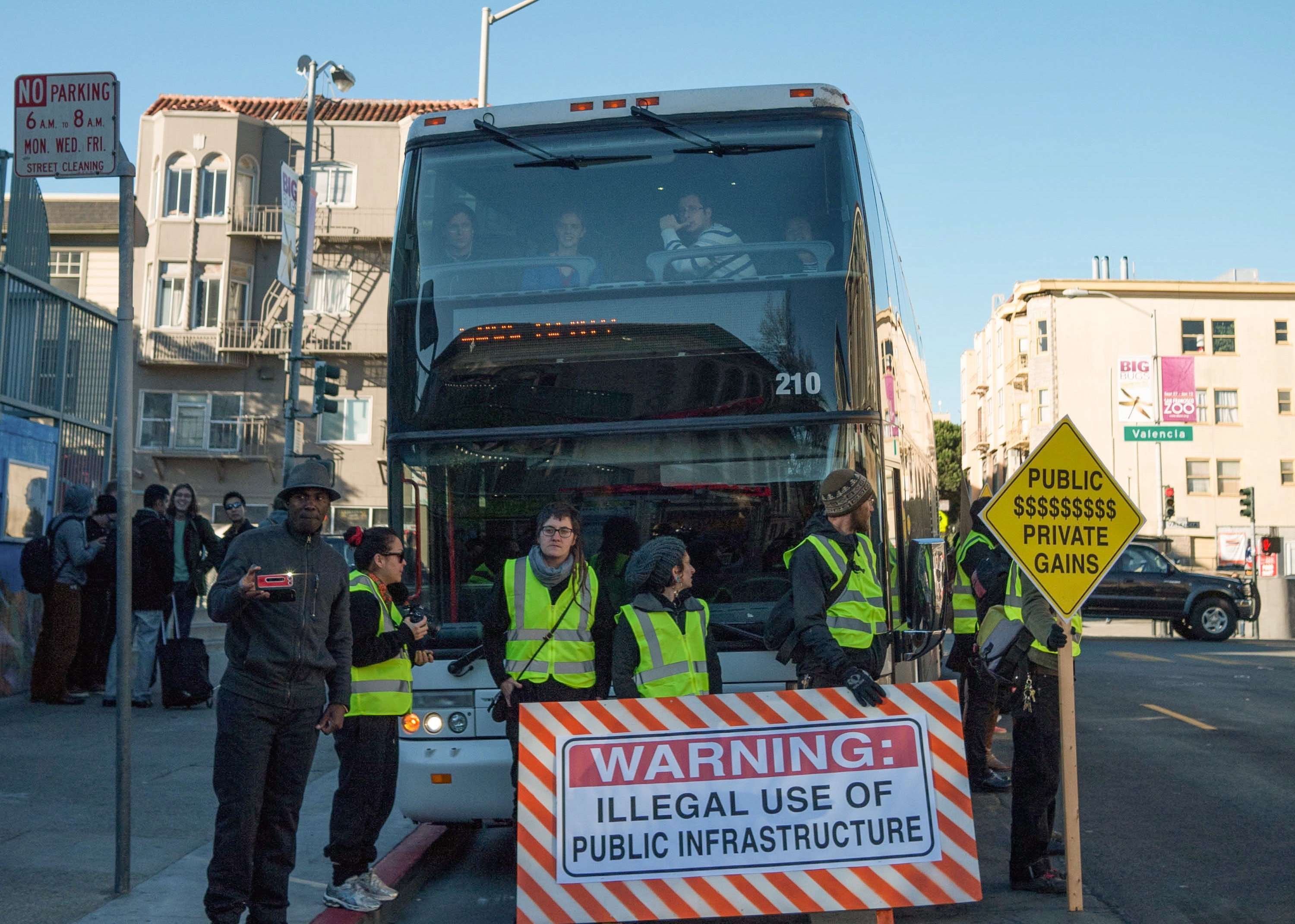 Tech bus protest, San Francisco, California, 2013. Explosive growth in the tech sector coupled with insufficient housing developments has led to increased living expenses in many Bay Area neighborhoods, displacing longtime residents. In December 2013 San Francisco residents protested against the buses used to shuttle employees to Oakland and Silicon Valley companies like Google, Apple, Yahoo!, and Facebook. As the Valley and the entire San Francisco Bay Area finds itself a symbol for all that is good and bad about technology, while facing its own societal issues as a result of the region's tech boom, some are questioning whether its state of mind is one that should be emulated. Credit: By Chris Martin