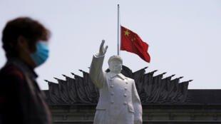 Quốc kỳ Trung Quốc và tượng Mao Trạch Đông, tại tỉnh Vũ Hán, Hồ Bắc, Trung Quốc, trong ngày Lễ Thanh Minh, 04/04/2020                via REUTERS - ALY SONG