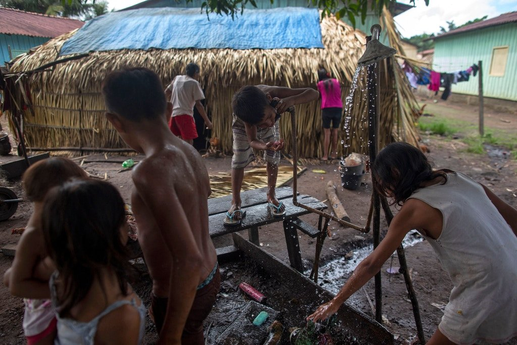 "Arara indigenous children drink water at the Laranjal tribal camp in Arara indigenous land, Pará, Brazil, on March 14, 2019. Isolated and off the grid, the nearly 200 residents of Laranjal village are among the some 800,000 indigenous people President Jair Bolsonaro says he wants to ""integrate into society."""