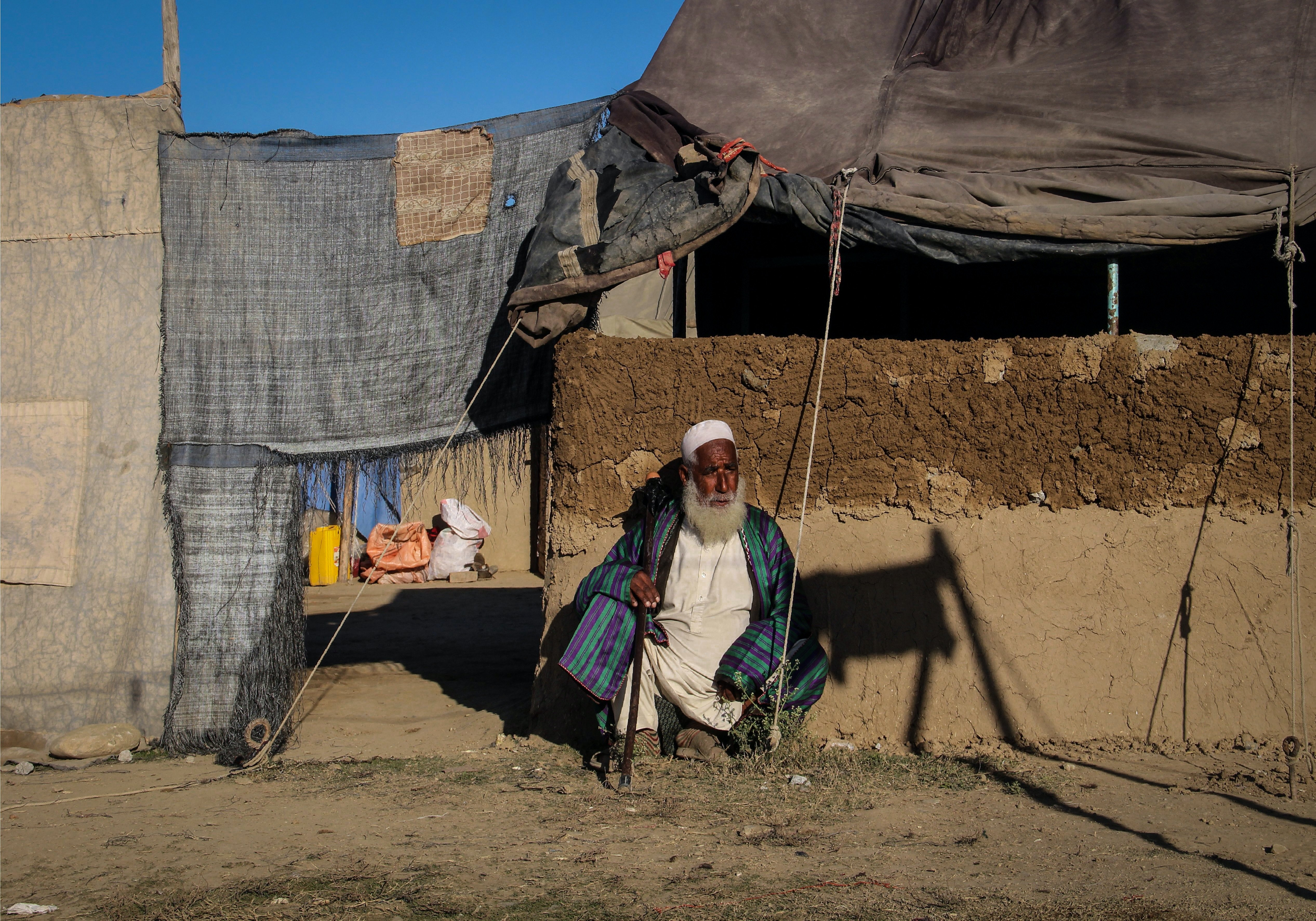 An internally displaced Afghan man sits against the wall of a mud house in Khost province on Dec. 2, 2019.