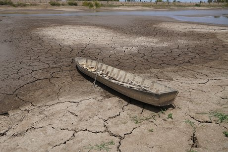 Chiếc xuồng người dân dùng giăng câu lưới nằm chỏng chơ giữa lòng hồ cạn nước. Ảnh: Hoàng Nam.
