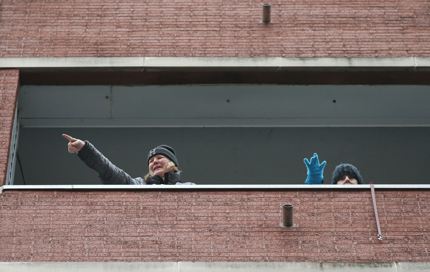 Katie Hession, left, and her mother, Joan, wave to neighbors from her father