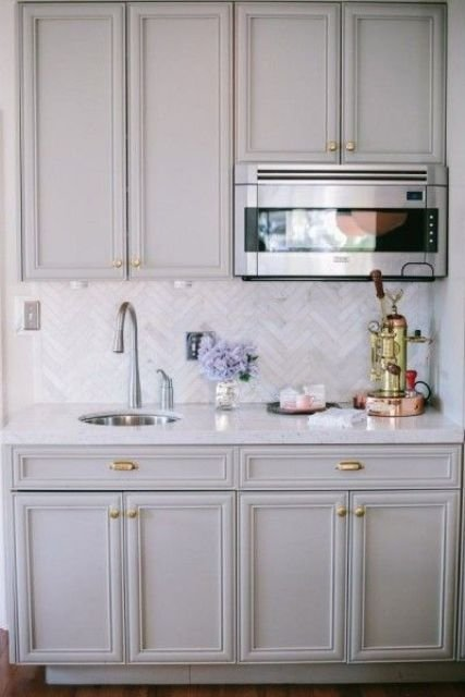 vintage grey kitchen cabinets and marble skinny tiles done in a chevron pattern for more eye-catchiness