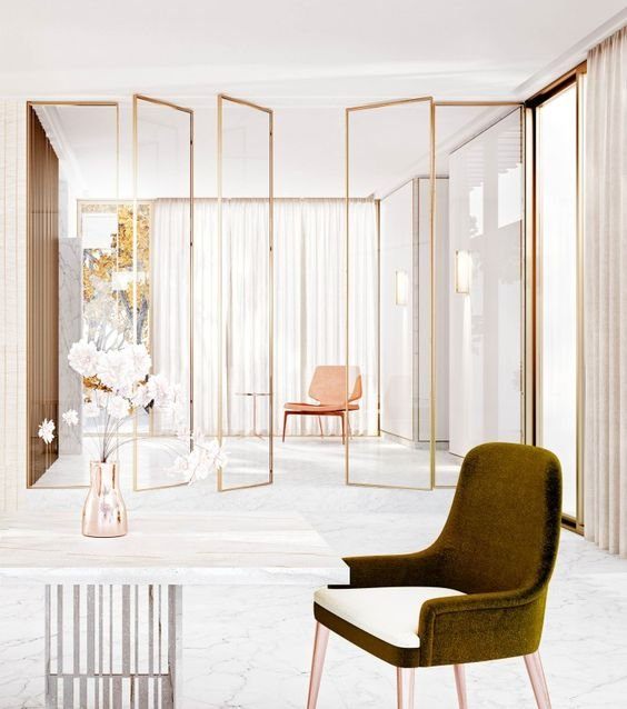 sheer glass screens with gold framing visually separate the spaces giving a slight glam feel to the space