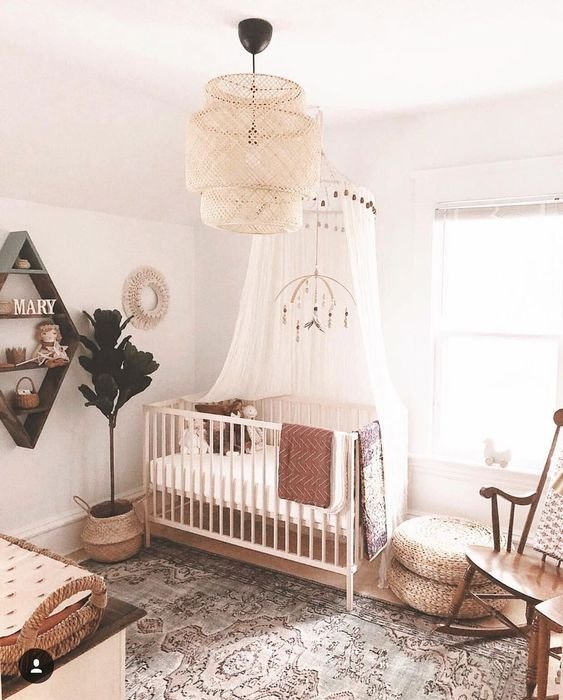 a farmhouse meets boho nursery with a statement wicker lamp, a printed rug, jute ottomans and a vintage rocker chairs