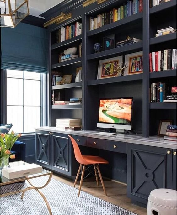 a rustic vintage home office with a dark blue wall unit and bright blue walls, a navy sofa and gold touches