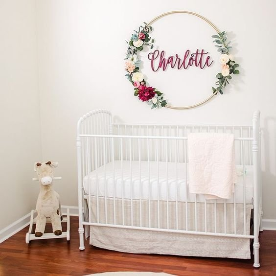 a name on the wall accented with an embroidery hoop with fake blooms and greenery is a chic idea