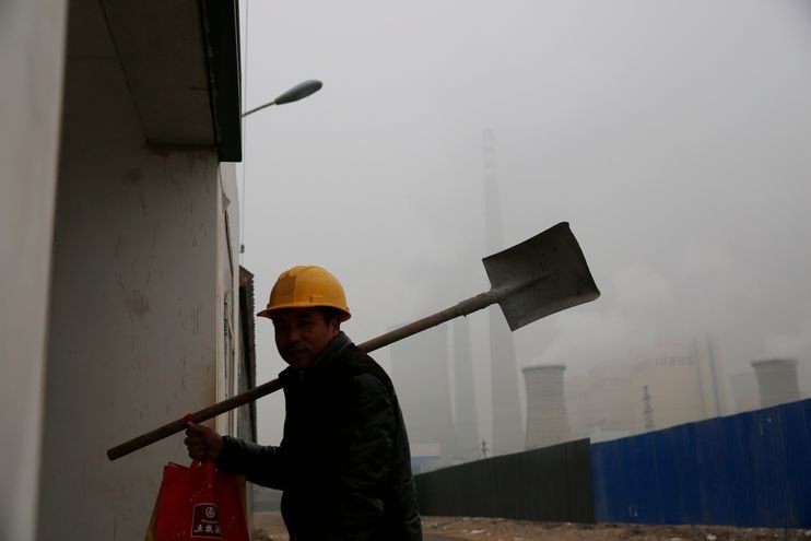 A Chinese migrant worker walks near a power plant on Sunday.