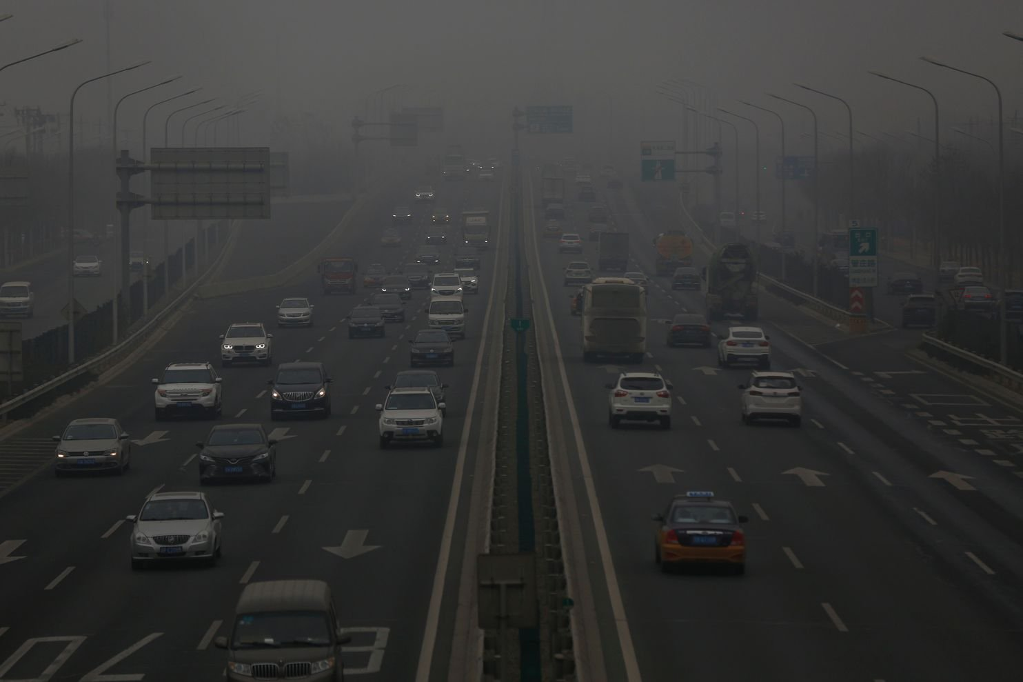 Vehicles travel along a highway during a polluted day in Beijing on Sunday.
