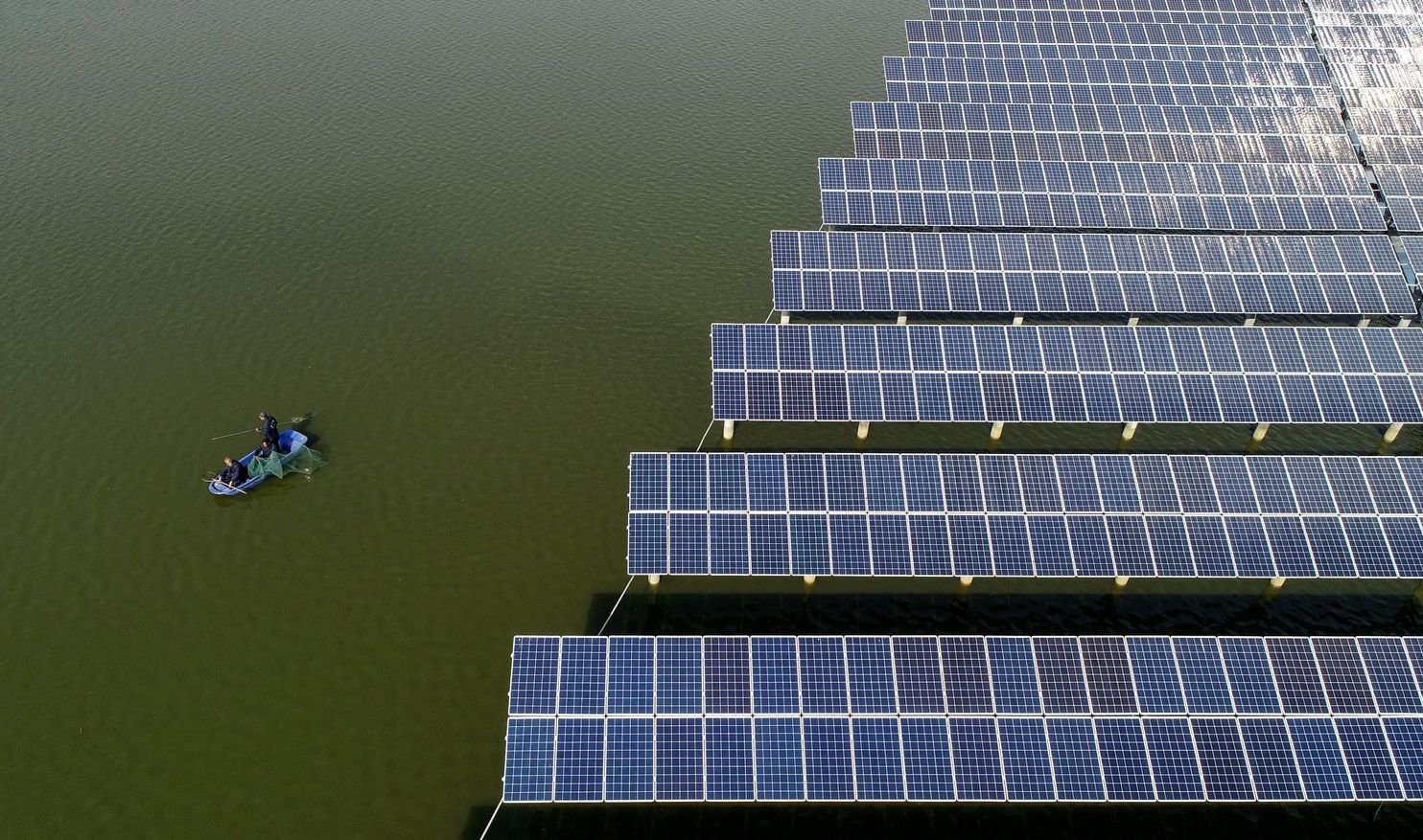 Chinese fishermen sit Nov. 14 next to a photovoltaic power station built on top of fish ponds in Yangzhou, in China