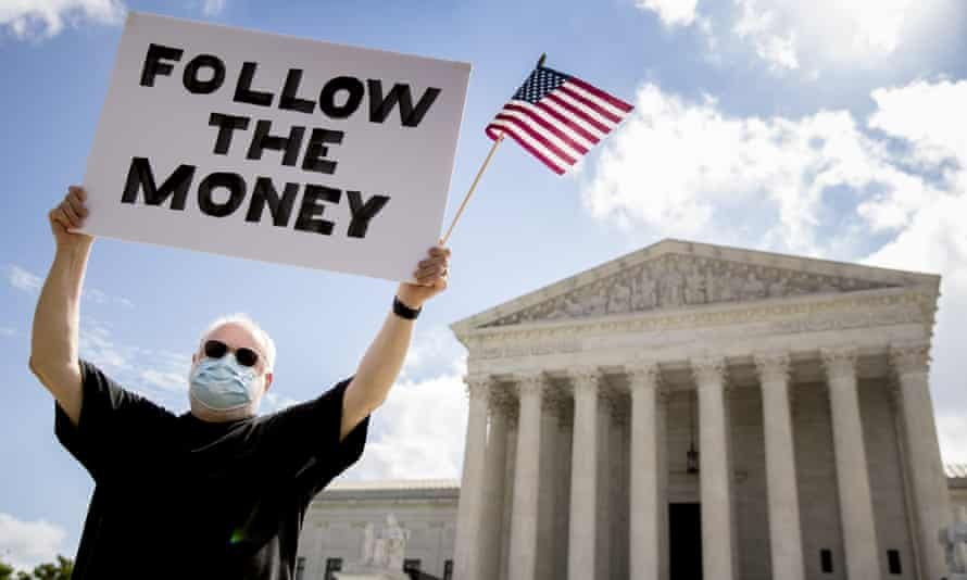 Bill Christeson holds up a sign that reads 'Follow the Money' outside the supreme court as it issued an initial ruling on the release of Donald Trump's tax returns last July. Photograph: Andrew Harnik/AP