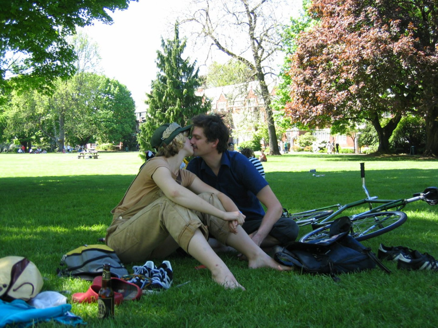 a person in overalls sitting on grass kissing a person in a polo shirt sitting next to a bike