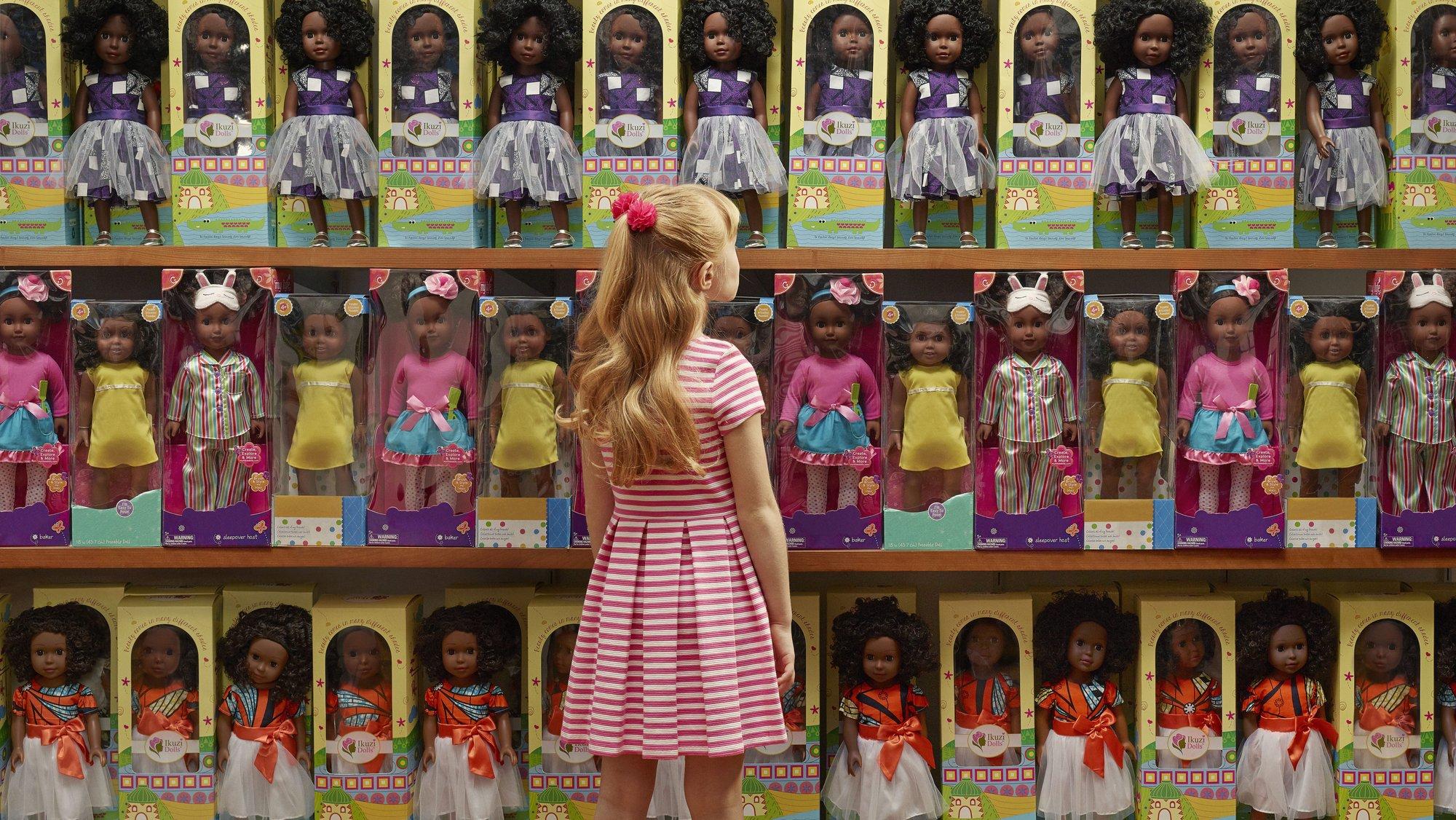 a white little girl looks up a shelves full of Black dolls
