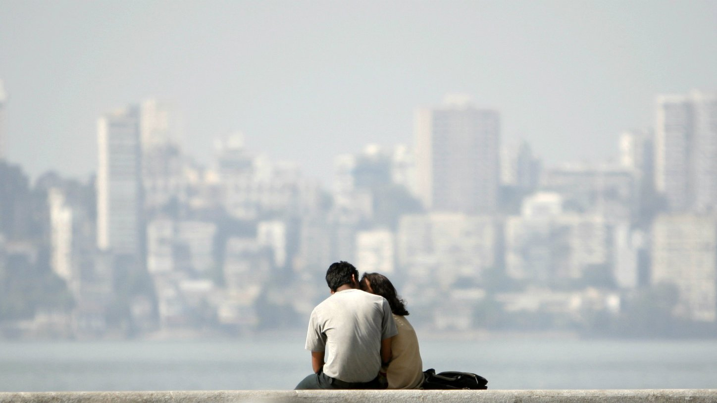 a couple kissing in front of a hazy city skyline