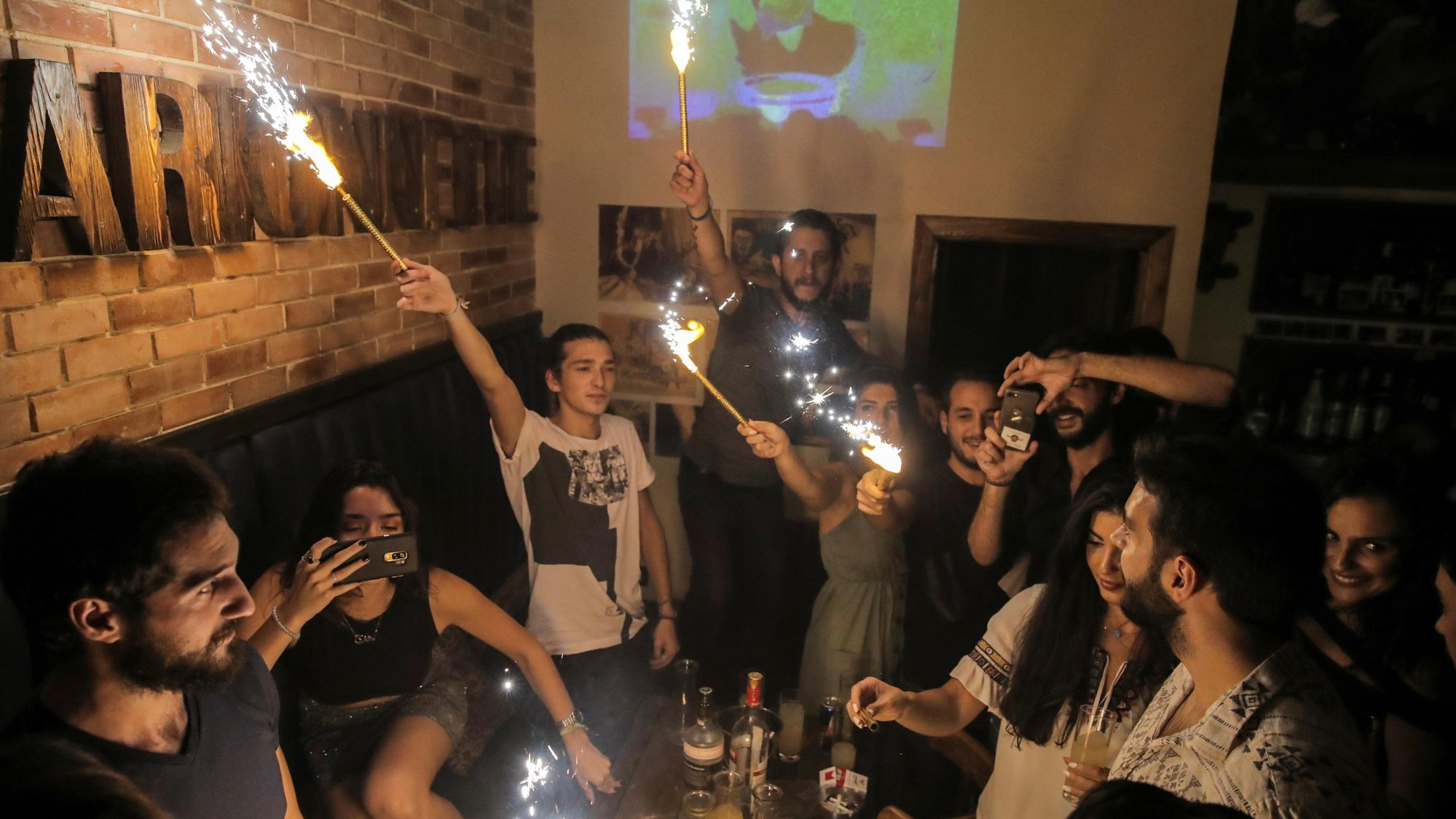 people gathered in a bar lighting sparklers and drinking