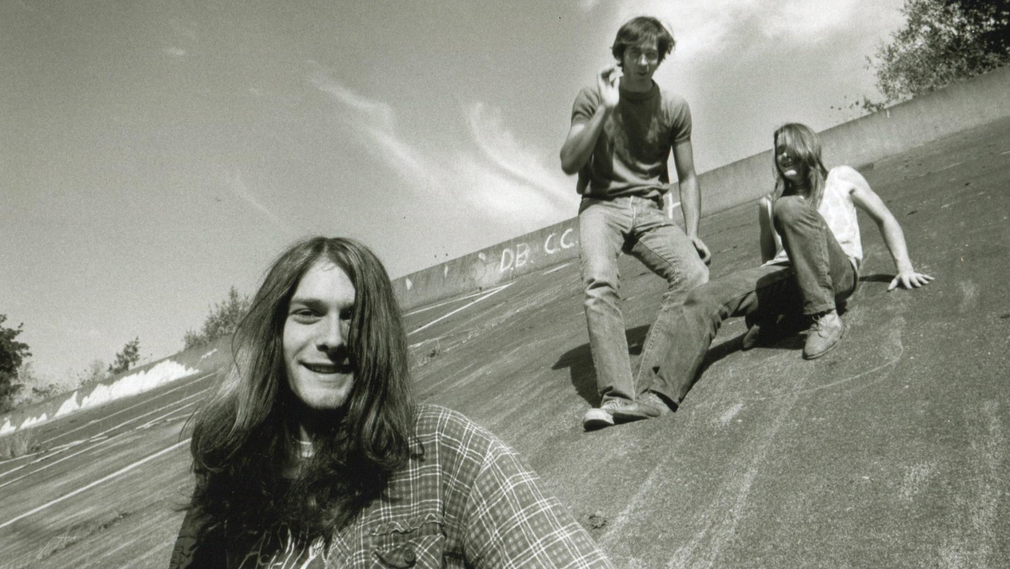 three guys with long hair and jeans smiling and sitting on a slope of cement