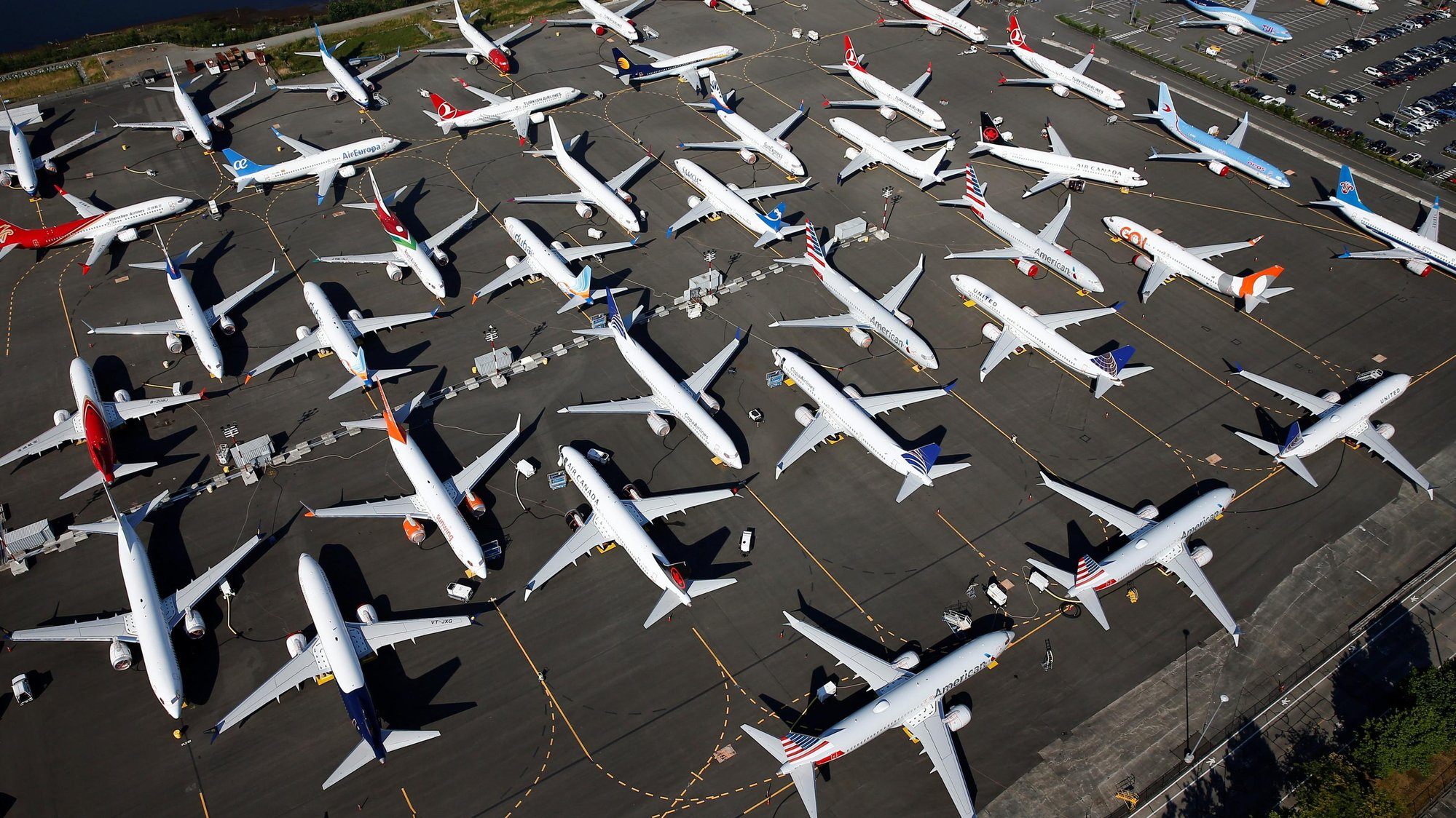 a grounded fleet of boeing planes on a sunny airfield