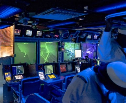 monitors in a ship as sailors look on