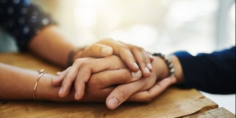 one person holding another person's hand in their own
