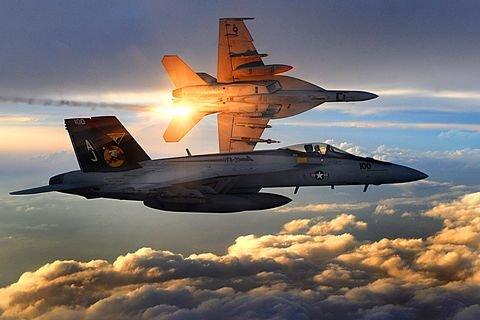 two jets flying high above sunlit clouds