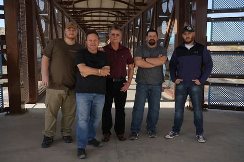 5 men standing and posing for a picture on what looks like a bridge