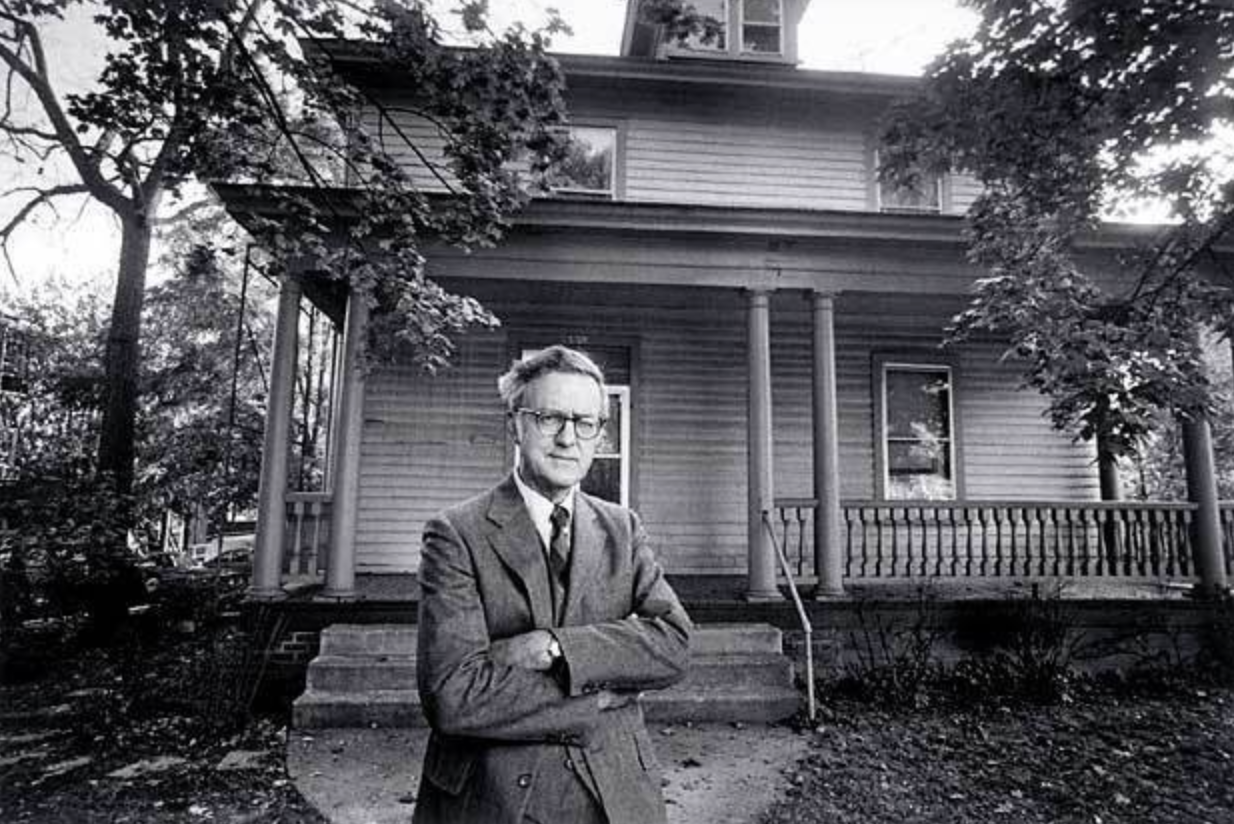 a black and white photo of a man in a suit posing in front of a house