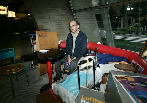 a man sits among his belongings inside an airport terminal