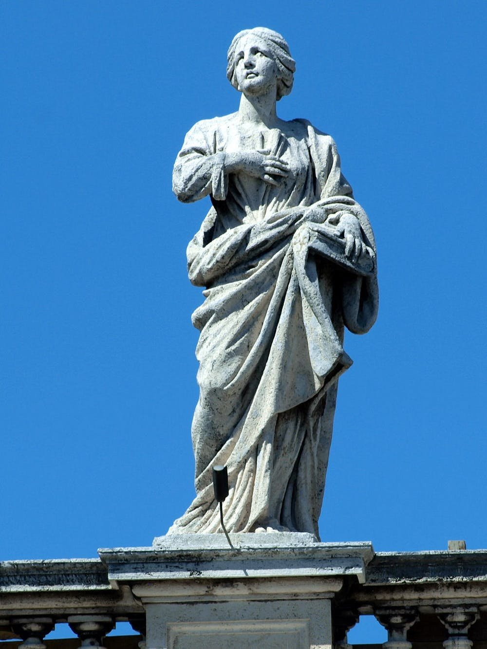 a statue of a woman in robes clutching a hand to her breast with a blue sky behind her