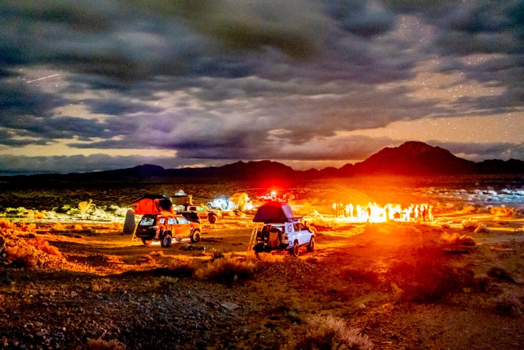 cars under a cloudy sky in open land
