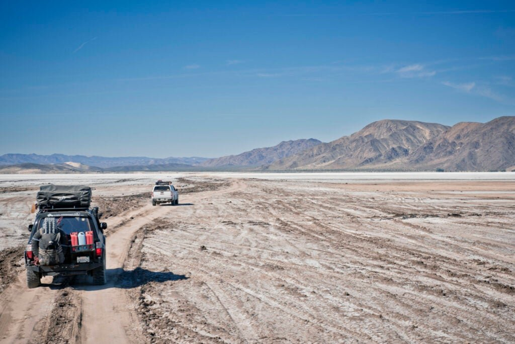 two loaded cars on a dirt path headed toward mountains